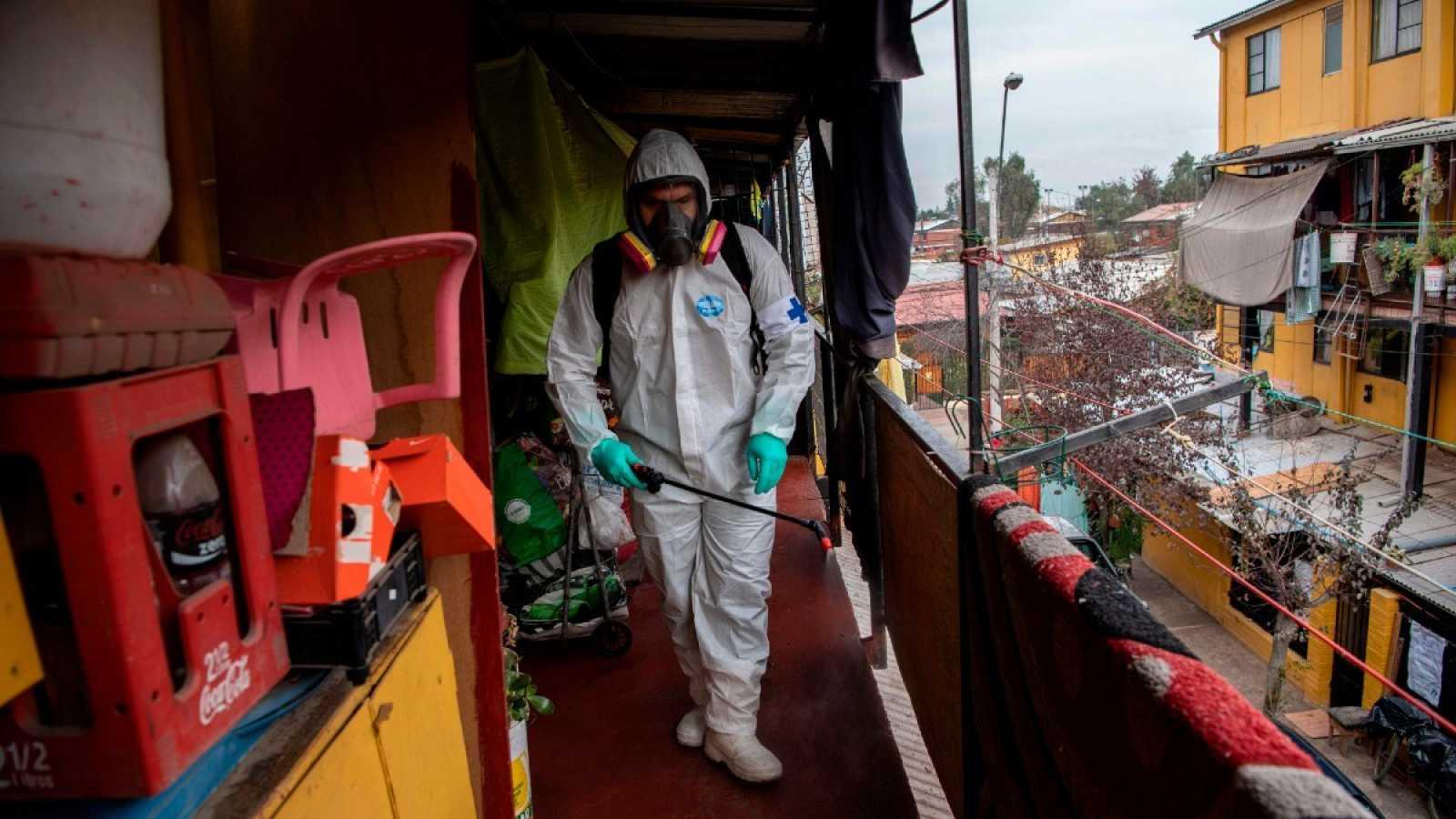Un trabajador municipal limpia y desinfecta una barrio pobre en Santiago
