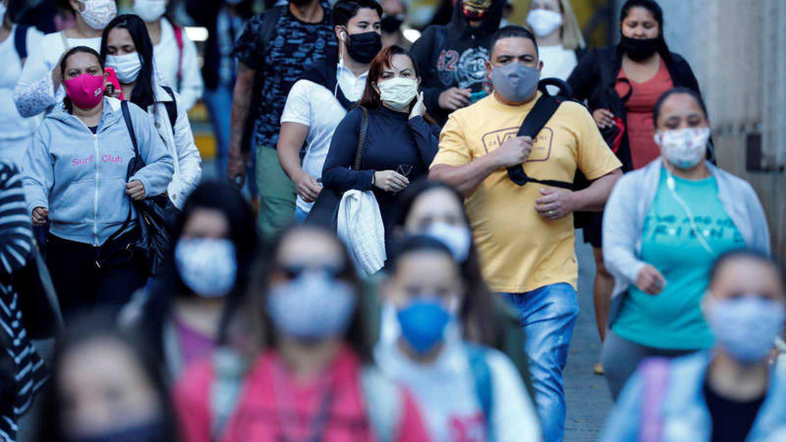 Personas con tapabocas caminan por una calle este viernes, en Sao Paulo (Brasil).