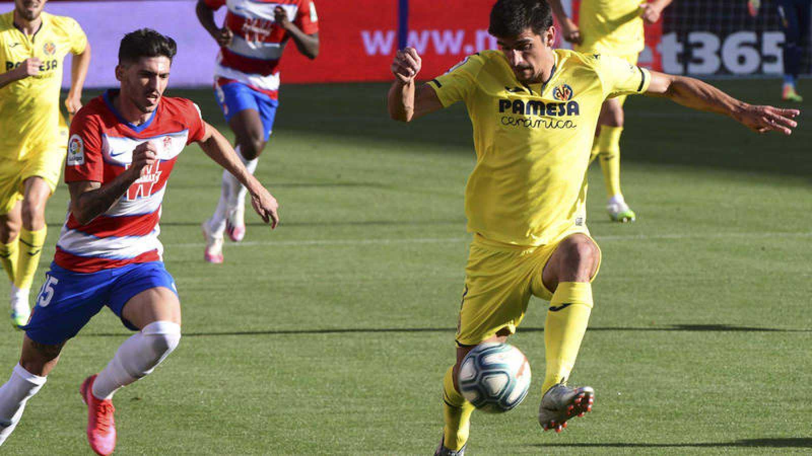 El delantero del Villarreal Gerard Moreno (d) controla el balón ante el defensa del Granada Carlos Neva