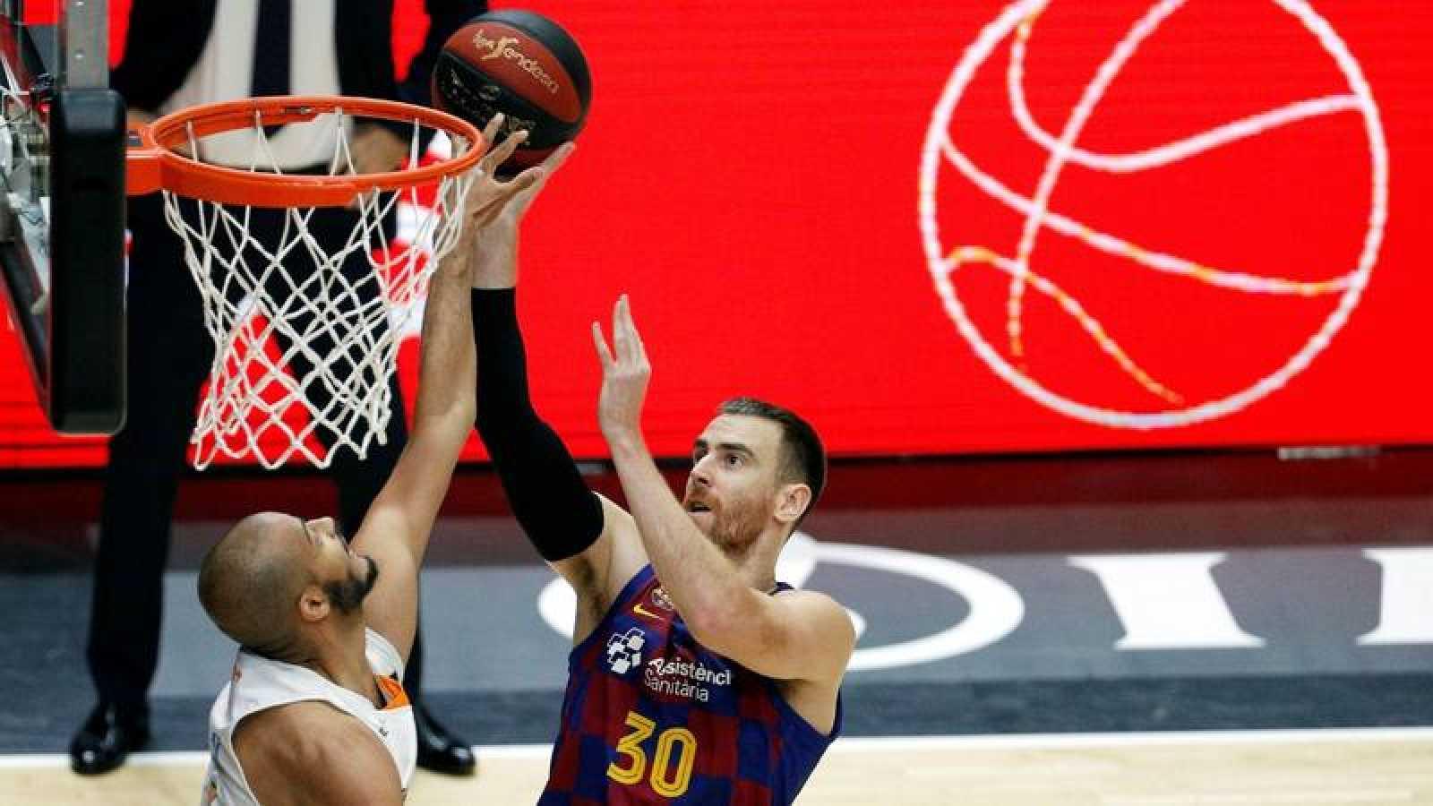 El alero estadounidense del Kirolbet Baskonia, Shavon Shields, trata de evitar el lanzamiento del alero del Barça, Victor Cláver.