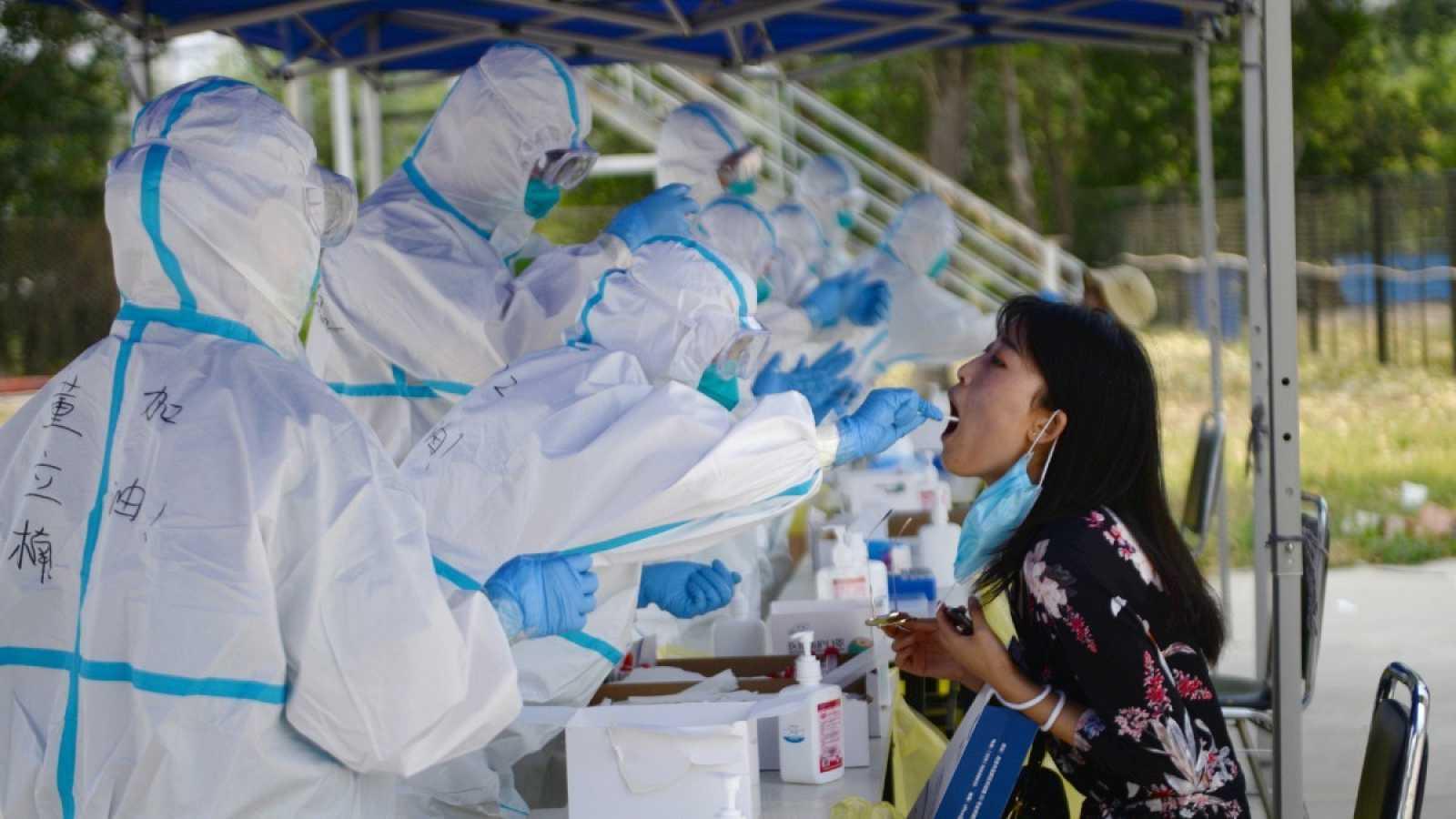 Trabajadores sanitarios chinos realizan pruebas de coranavirus a una residente, después de un brote en Pekín