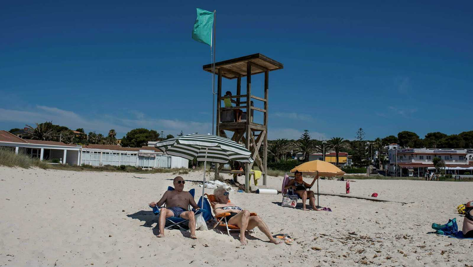 """Varias personas disfrutan en la playa del primer día de la denominada """"nueva normalidad"""" en la playa de Punta Prima, Menorca."""