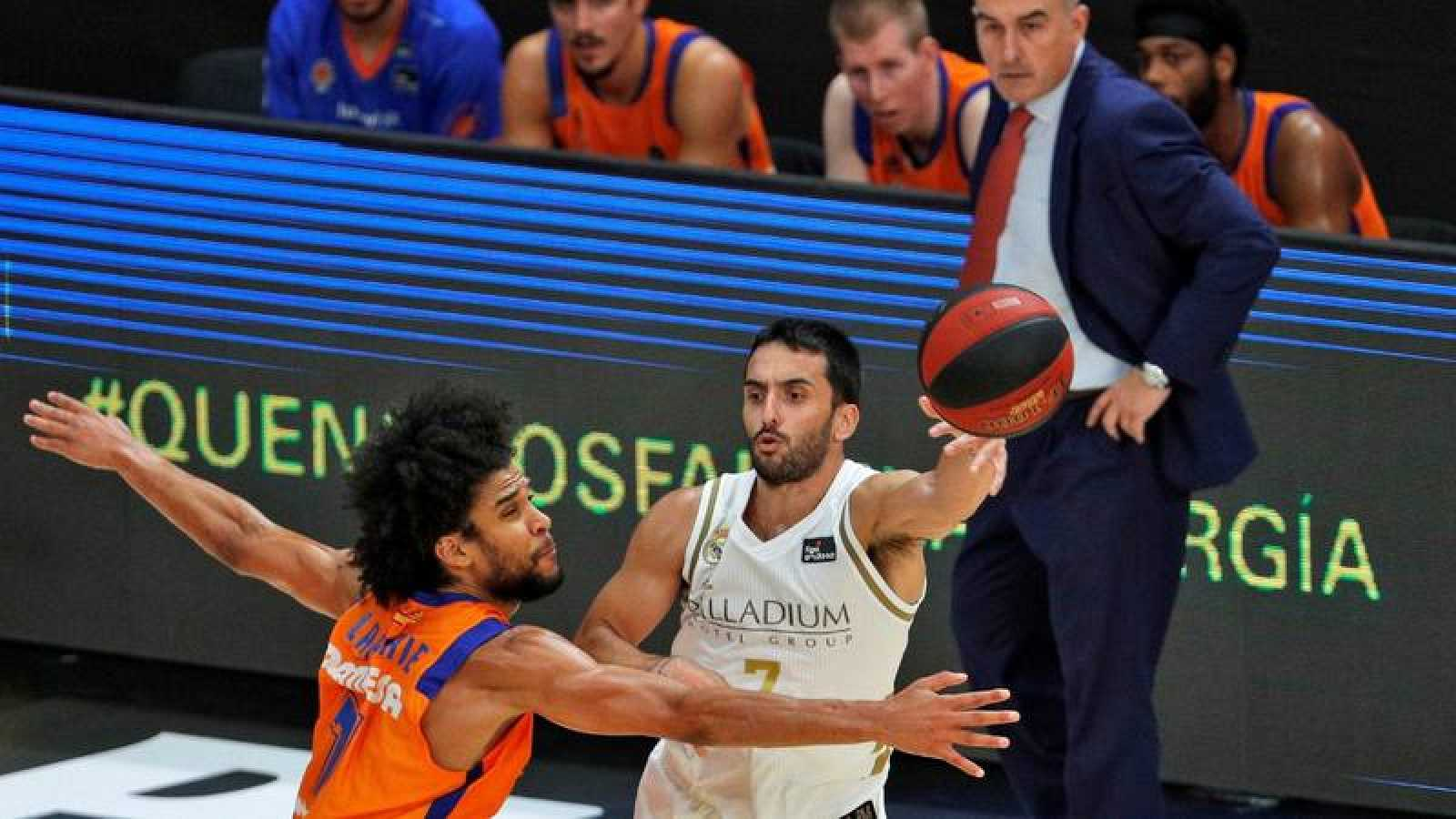 El base argentino del Real Madrid, Facundo Campazzo, asiste a un compañero ante el ala pívot francés del Valencia Basket, Louis Labeyrie.