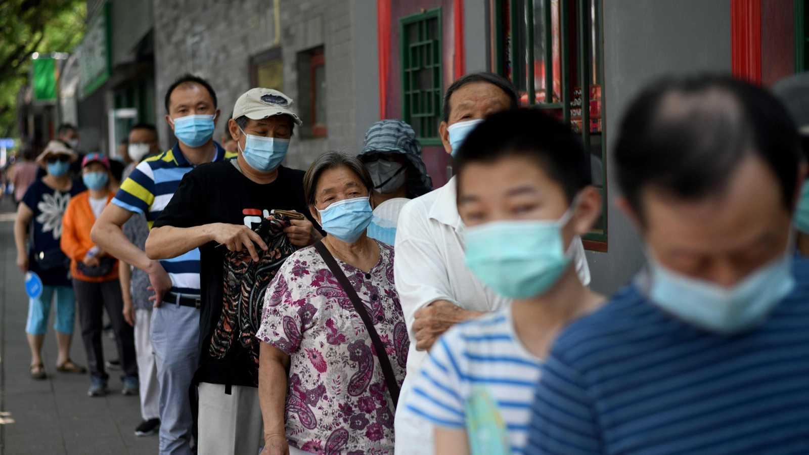 Ciudadanos chinos con mascarilla hacen cola para realizarse la prueba del coronavirus en Pekín