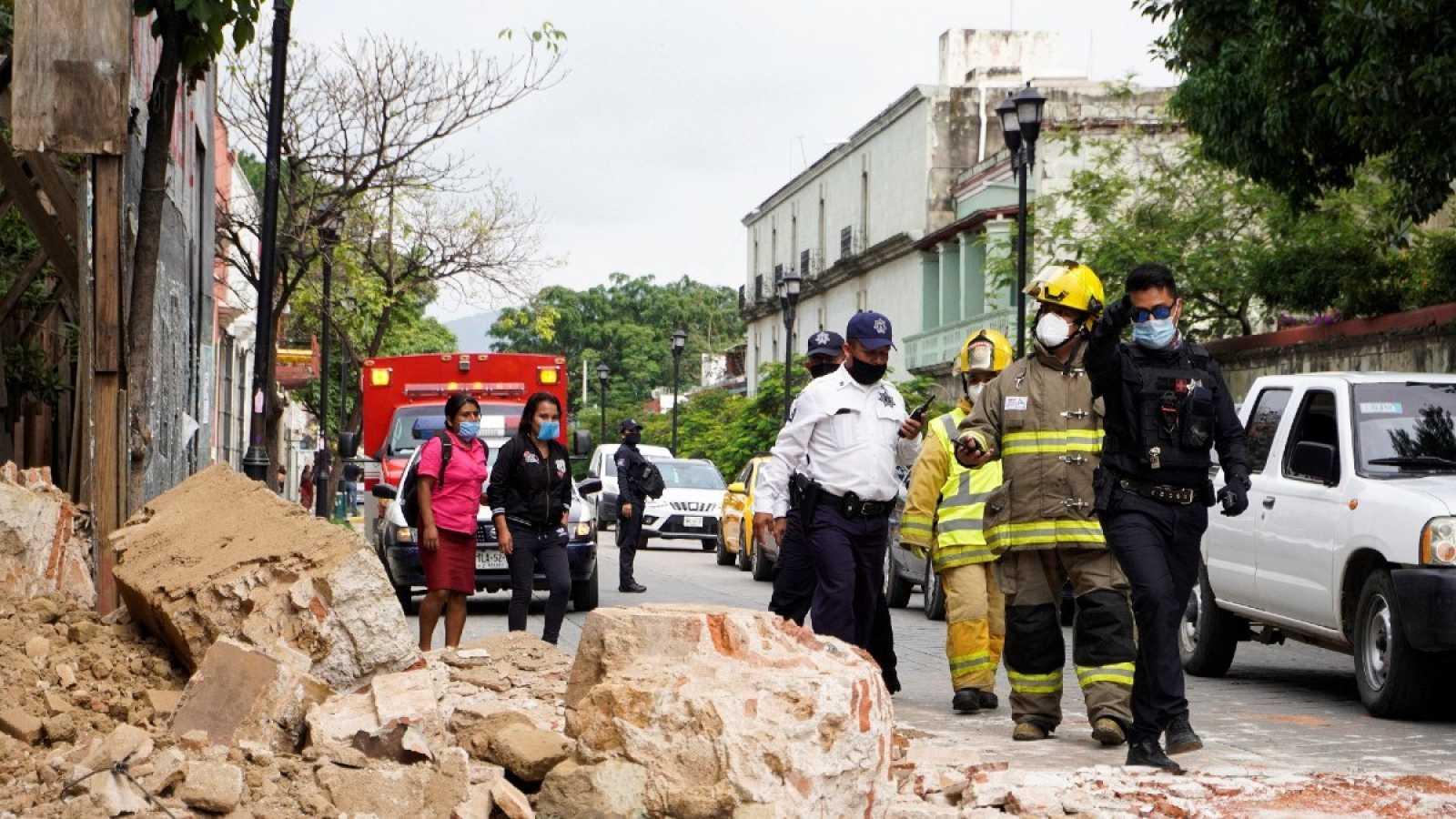 Miembros de la policía y de los bomberos observan los daños causados por el terremoto de 7,5, en la ciudad de Oaxaca (México).