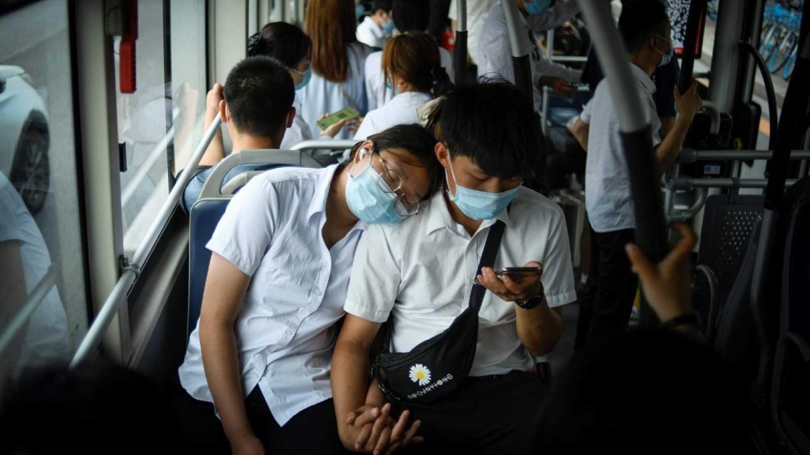 Una pareja con mascarilla viaja en un autobús en hora punta en Pekín