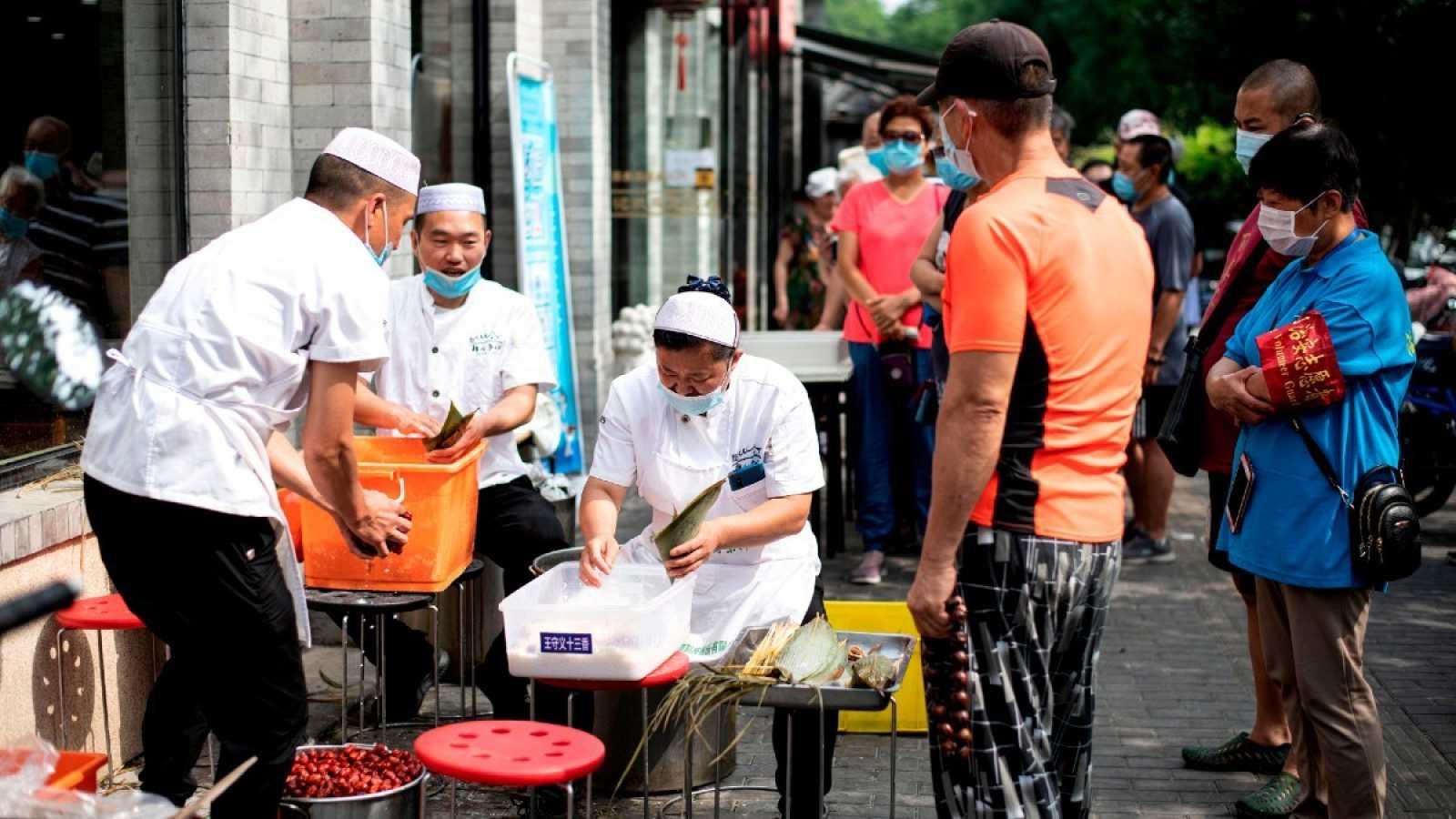 Trabajadores con mascarillas preparan comida en las calles de Pekín