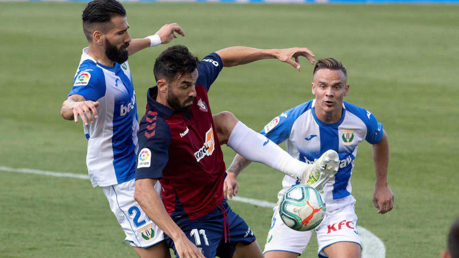 El jugador del Osasuna Enric Gallego (c) disputa un balón con el defensa griego del Leganés, Siovas, y con Roque Mesa (dcha).