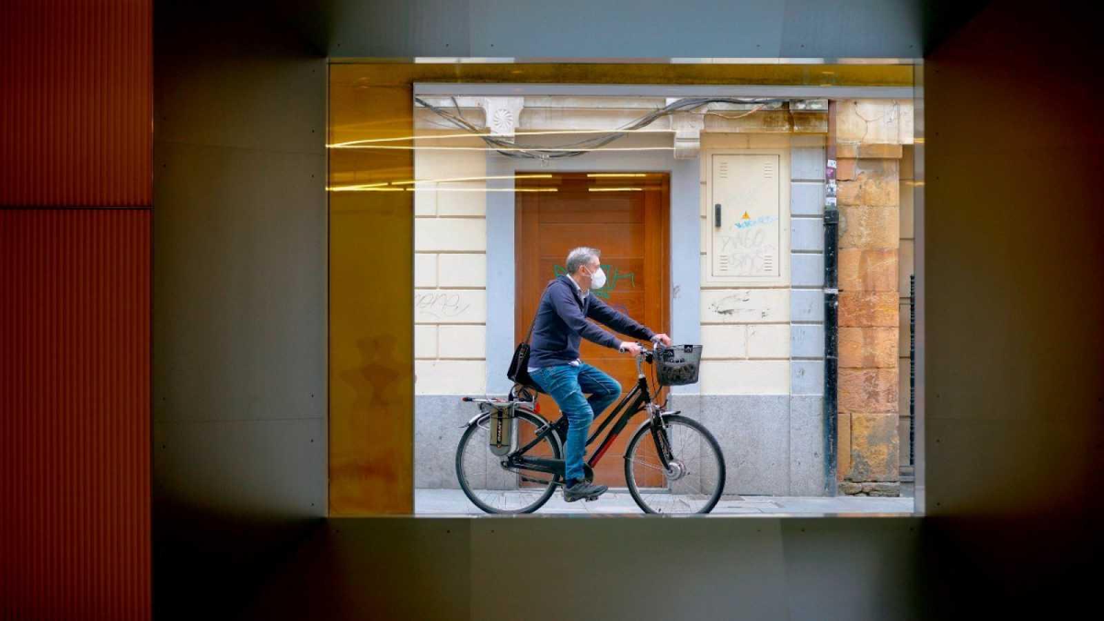 Un hombre con mascarilla pasea en bicicleta por una calle