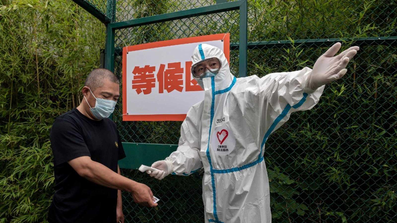 Un hombre con mascarilla se somete a un control de temperatura corporal por un trabajador sanitario vestido con un equipo de protección personal en Pekín
