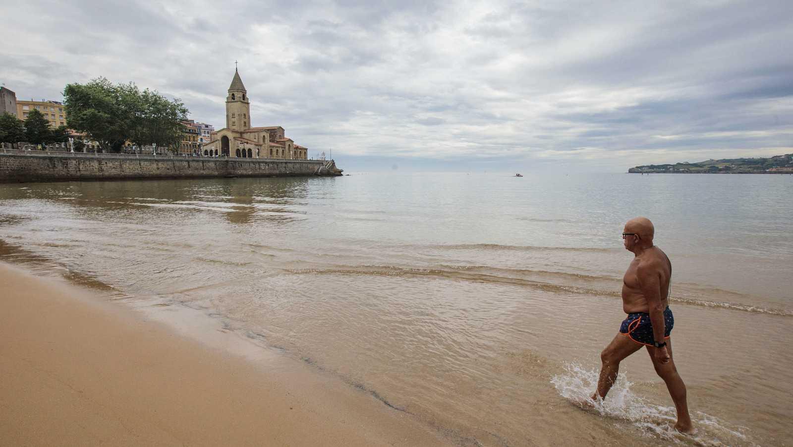 Un hombre avanza por la playa de San Lorenzo de Gijón, vacía en un día nublado y dejando atrás la fase dura del confinamiento en España.