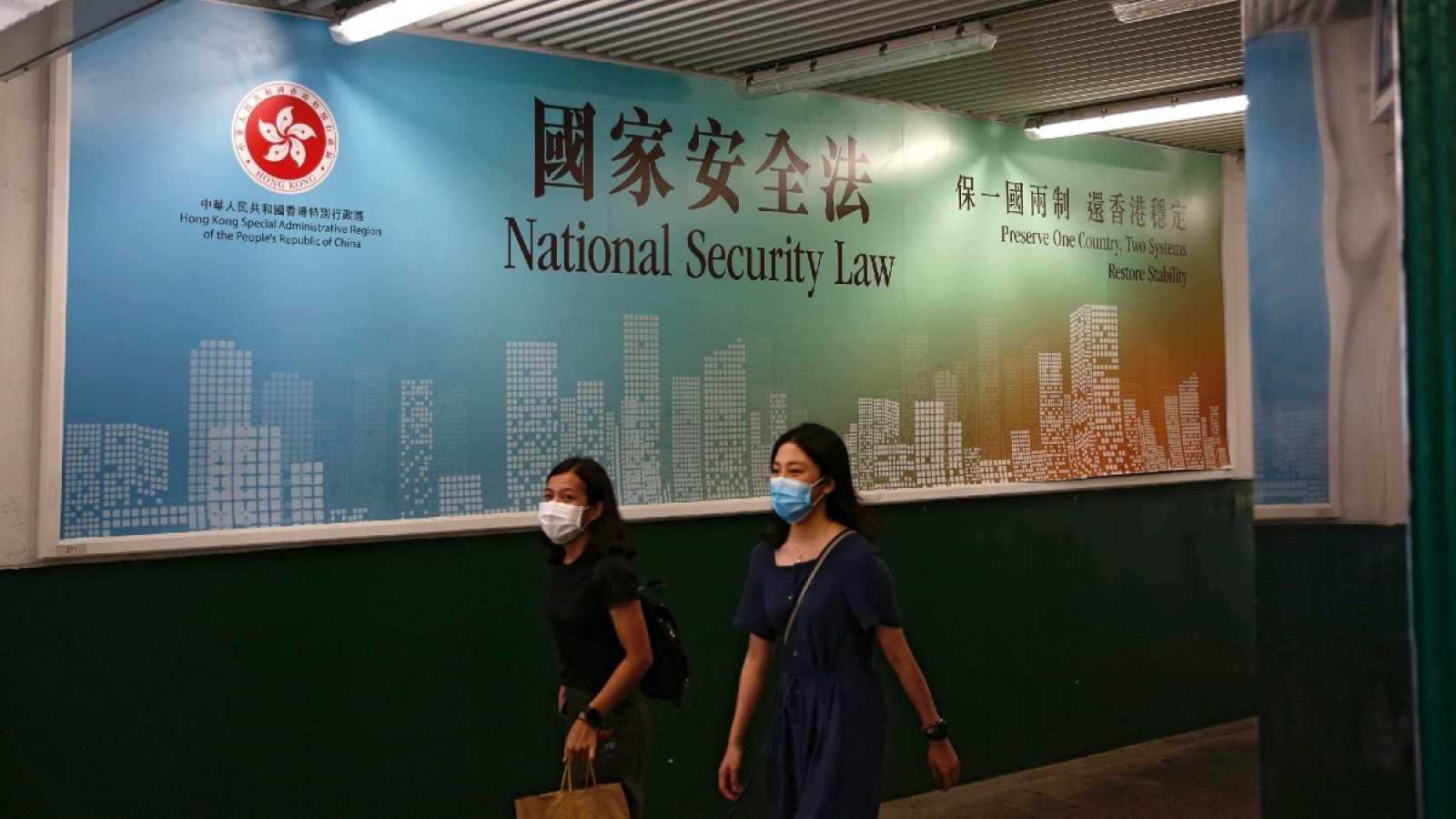 Mientras se debate la aprobación de la ley de seguridad nacional, dos mujeres pasan por delante de un anuncio del gobierno en defensa de su entrada en vigor en Hong Kong