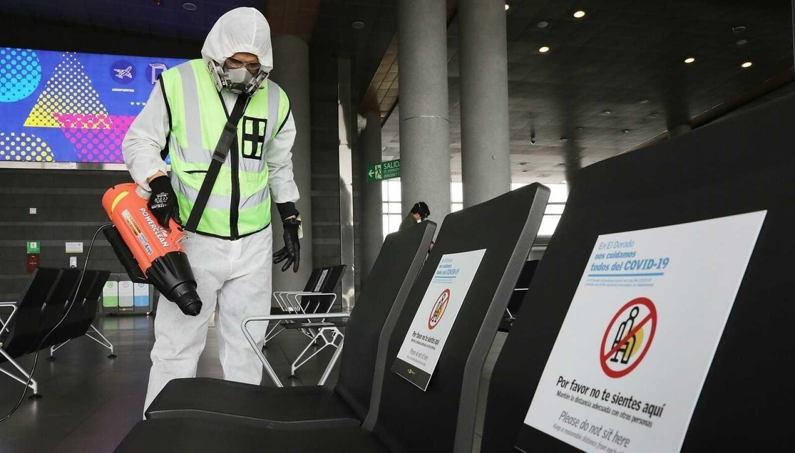 Un empleado desinfecta la sala de espera en el Aeropuerto Internacional El Dorado, en Bogotá (Colombia).