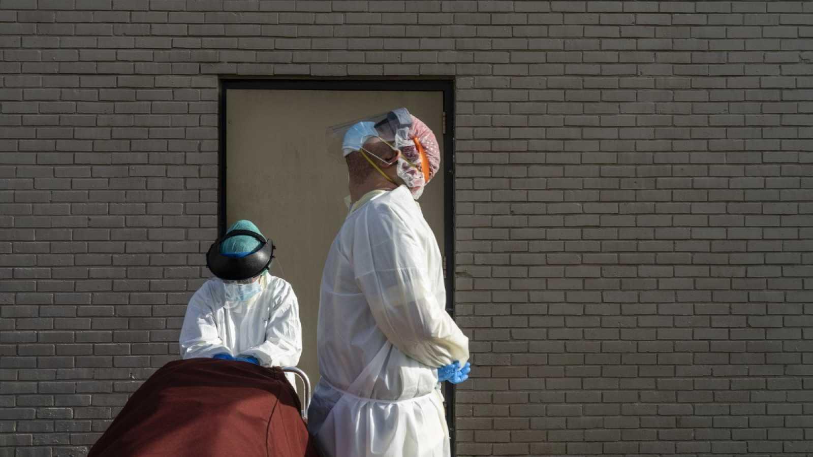 Dos sanitaros con equipo de protección esperan a que un coche recoja a un paciente fallecido en un hospital de Houston, Texas