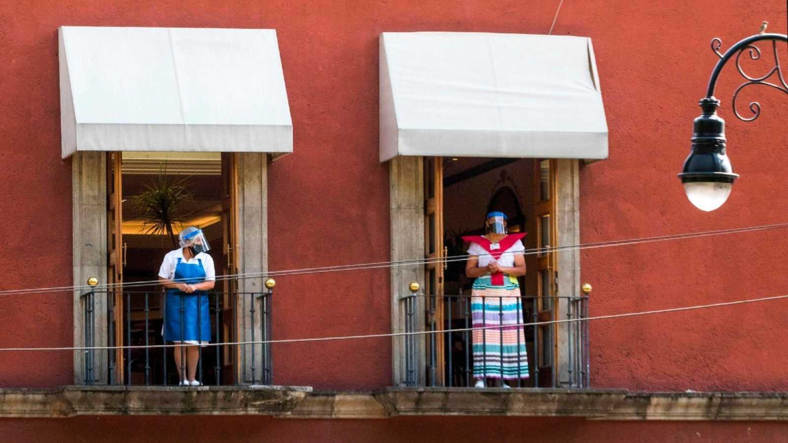 Dos trabajadoras en el balcón de un restaurante en Ciudad de México, el 1 de julio de 2020, durante la pandemia de COVID-19
