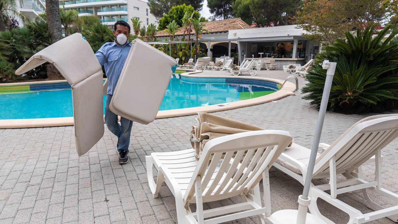 Un trabajador de un hotel prepara las zonas exteriores del complejo para recibir a los turistas