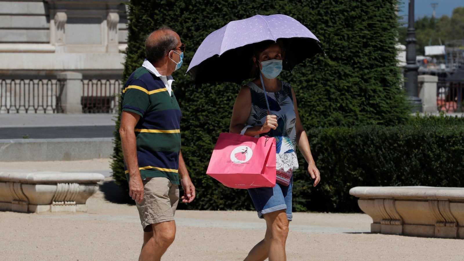 Dos personas pasean por el centro de Madrid durante la ola de calor