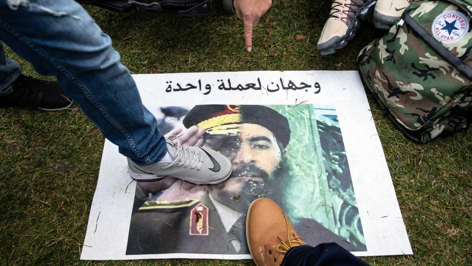 """Varias personas pisan una pancarta con un retrato con una mitad del mariscal National Army Khalifa Haftar y el líder del ISIS Abu Bakr al-Baghdadi con la frase """"Dos caras de la misma moneda""""."""