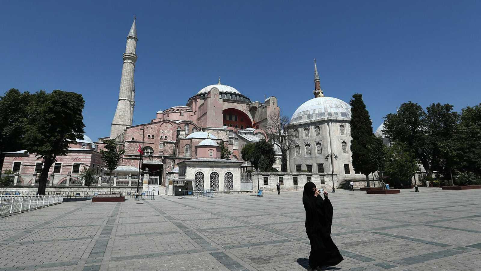 Una mujer vestida con un hiyab toma fotografías frente el Museo de Santa Sofía en Estambul.