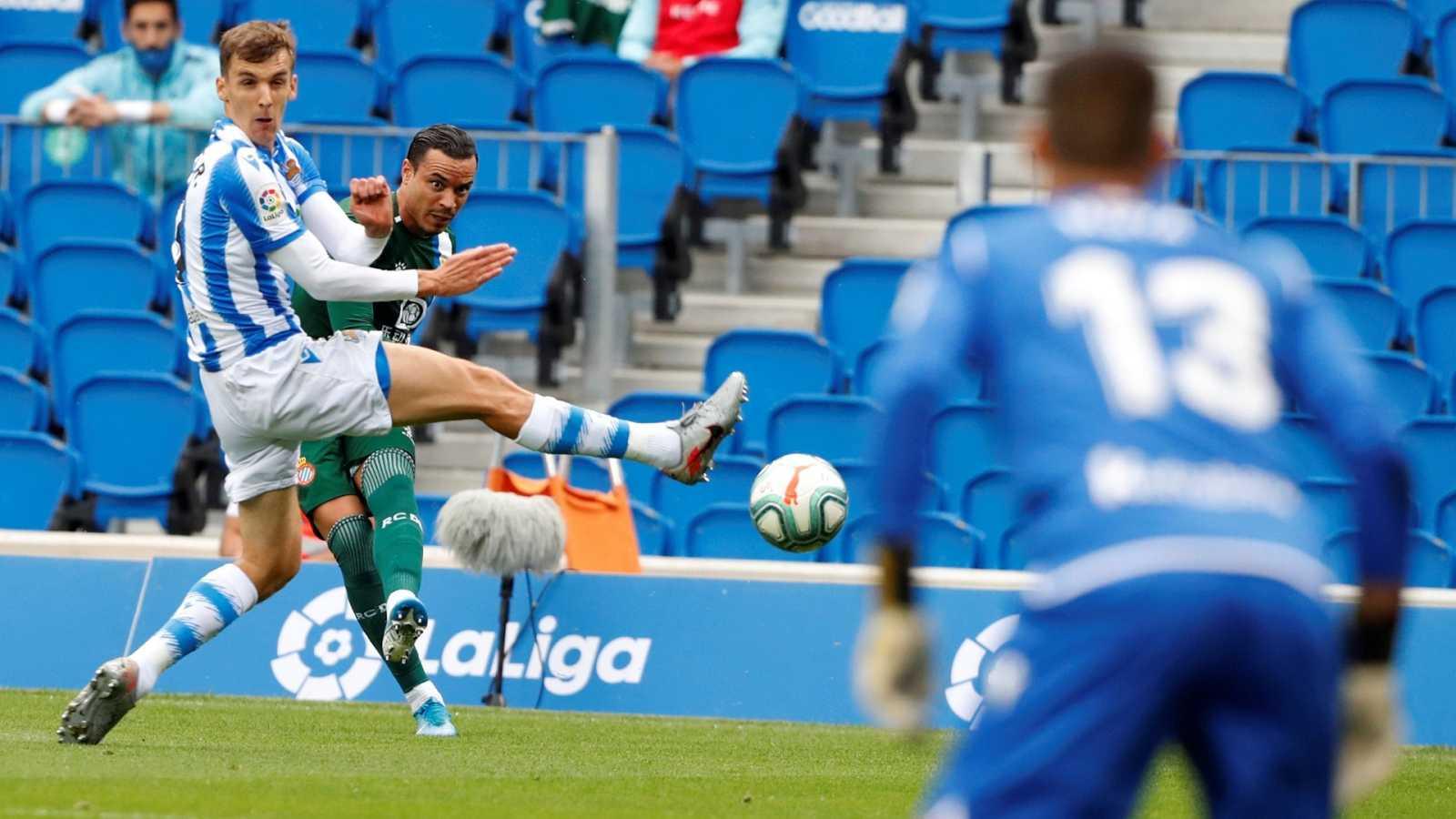 El delantero del Espanyol Raúl de Tomás (detrás) intenta un pase ante el defensa de la Real Sociedad Diego Llorente