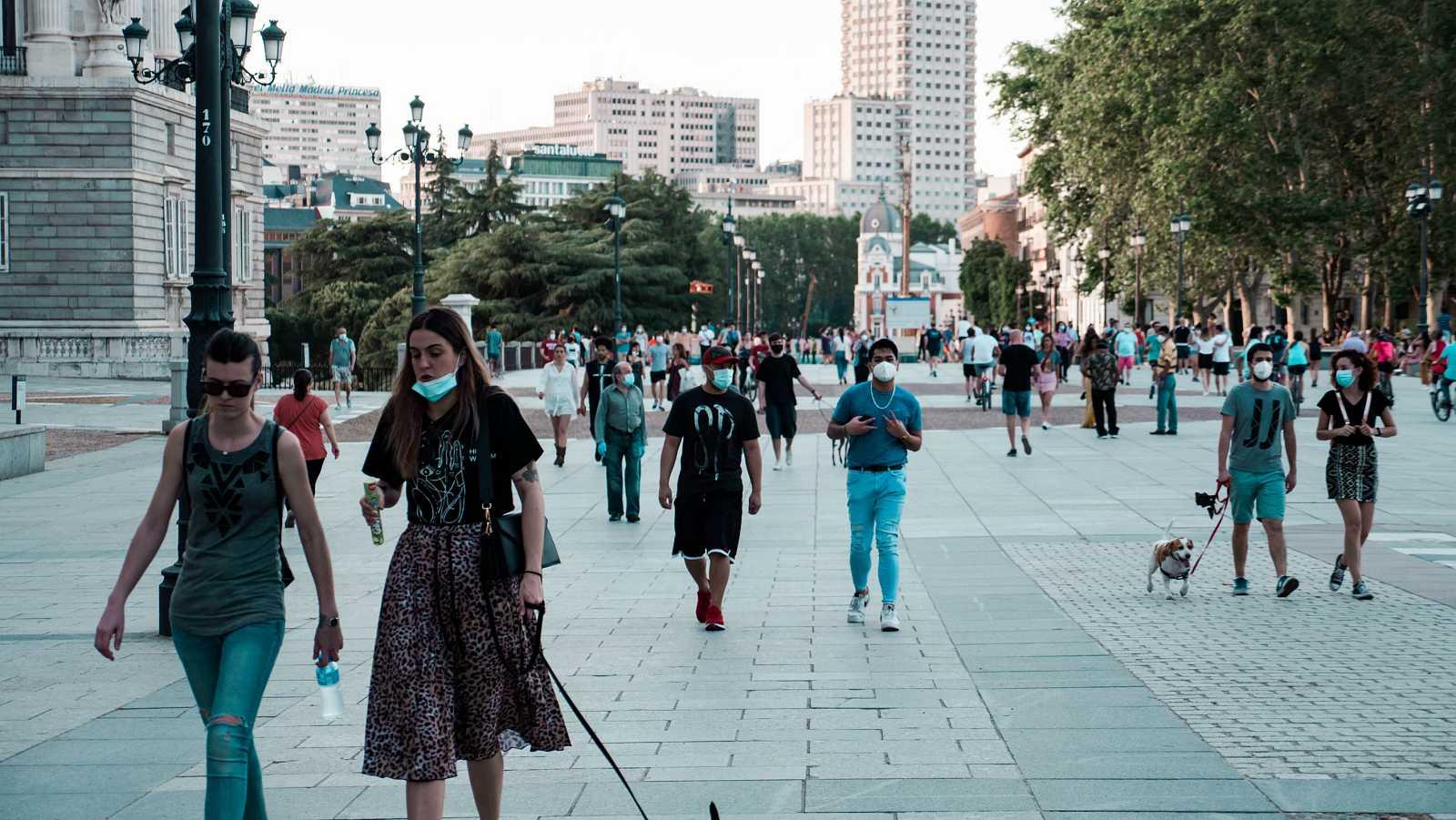 Gente paseando con mascarillas en la Plaza de Oriente de Madrid.