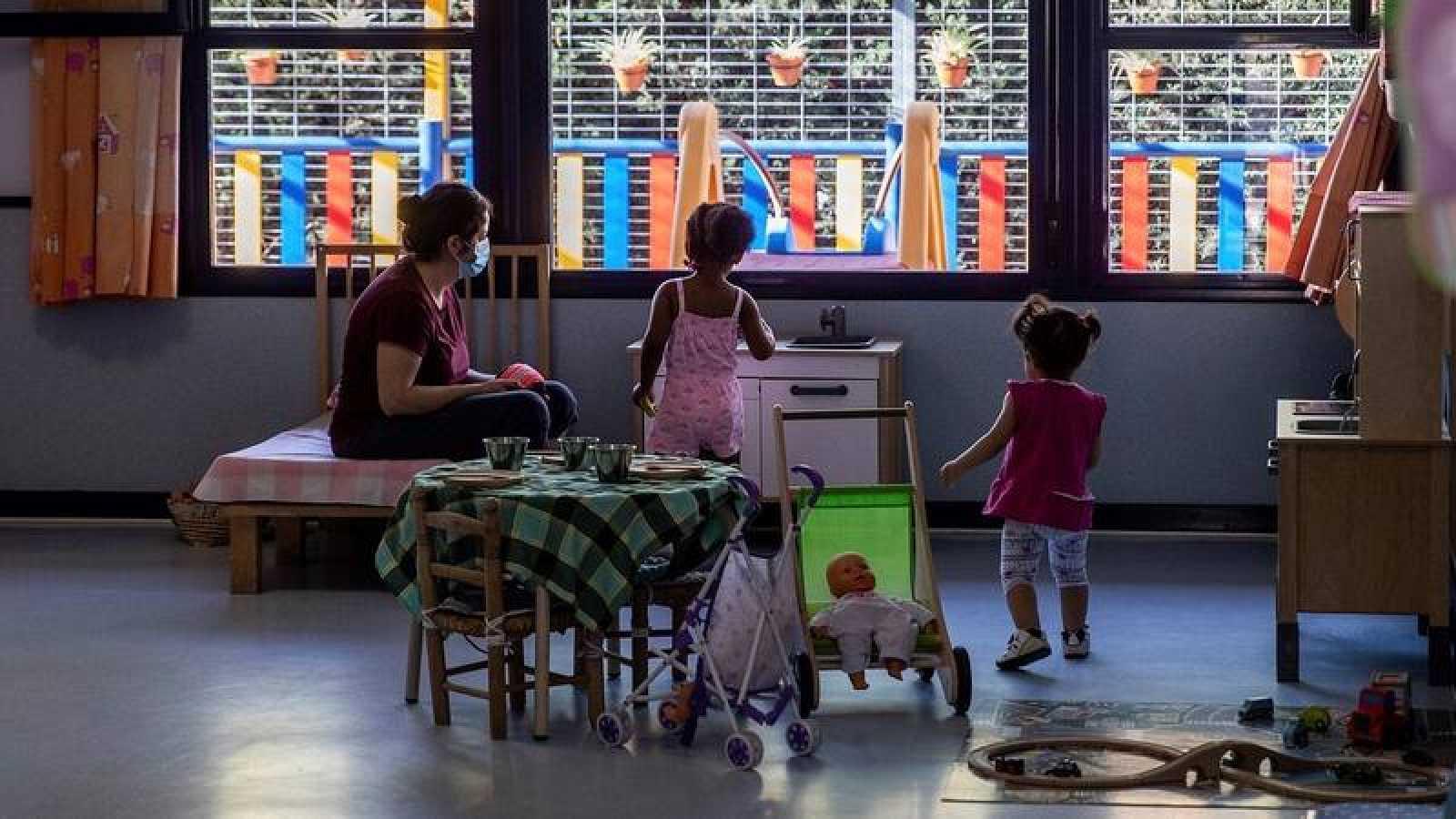 Una educadora con dos alumnas durante la reapertura de la escuela infantil Las Viñas en Pozuelo, Madrid