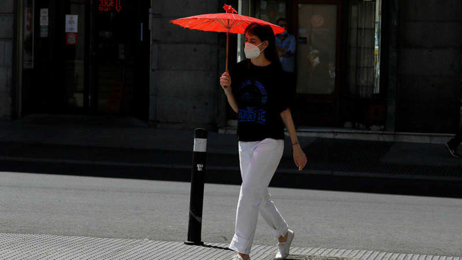 Una viandante se protege del sol con una sombrilla en el centro de Madrid.