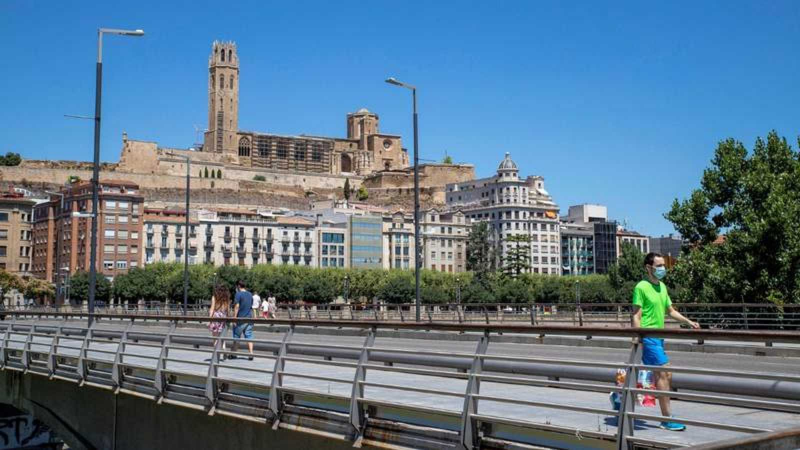 Un hombre camina por las calles de Lleida con mascarilla.