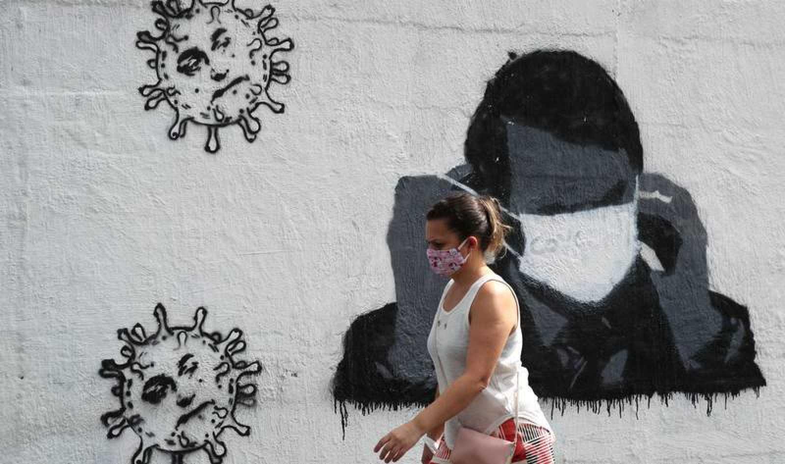 Una mujer camina frente a un mural del coronavirus en Río de Janeiro