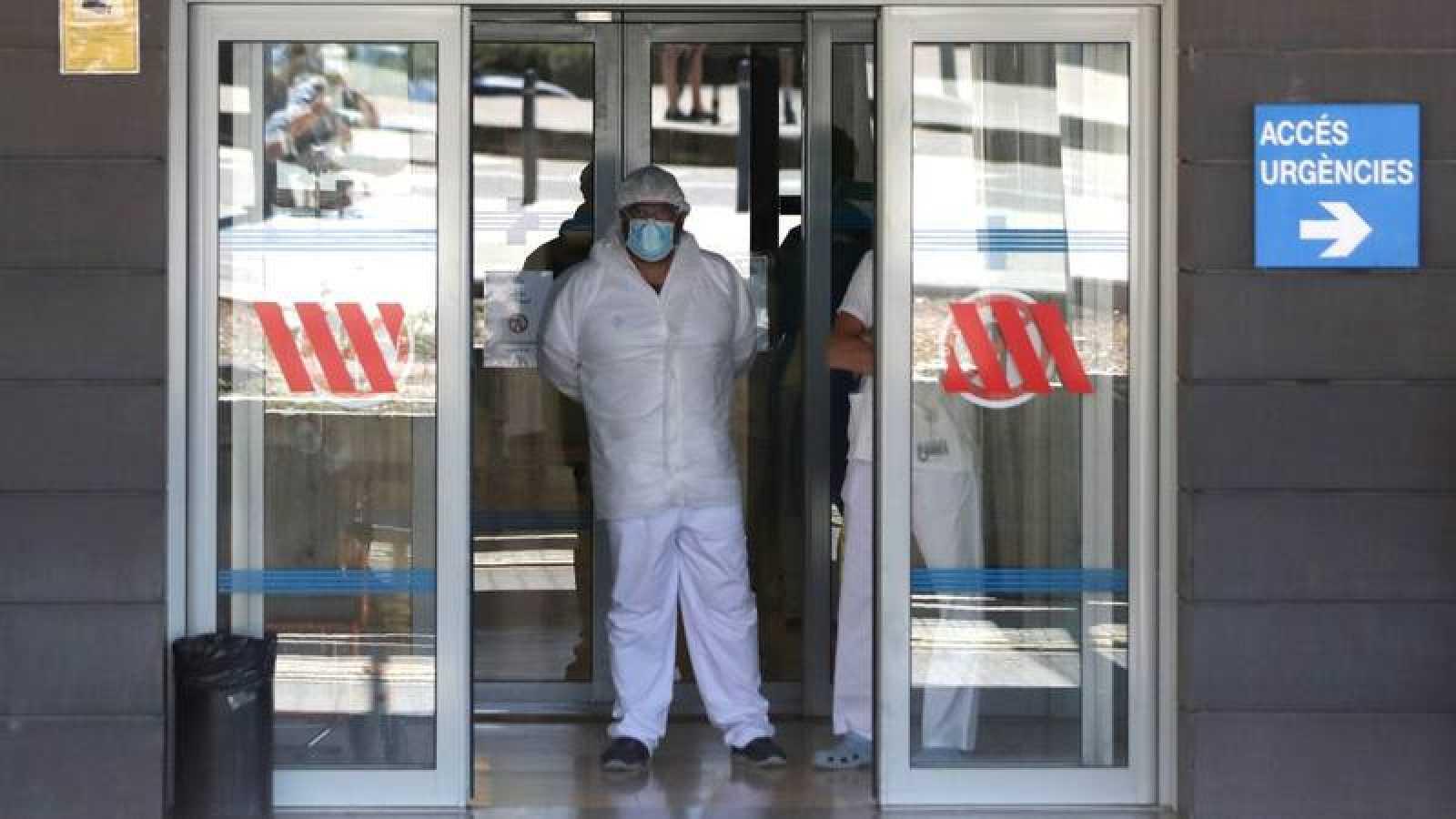 Un trabajador sanitario espera a las puertas de un hospital.