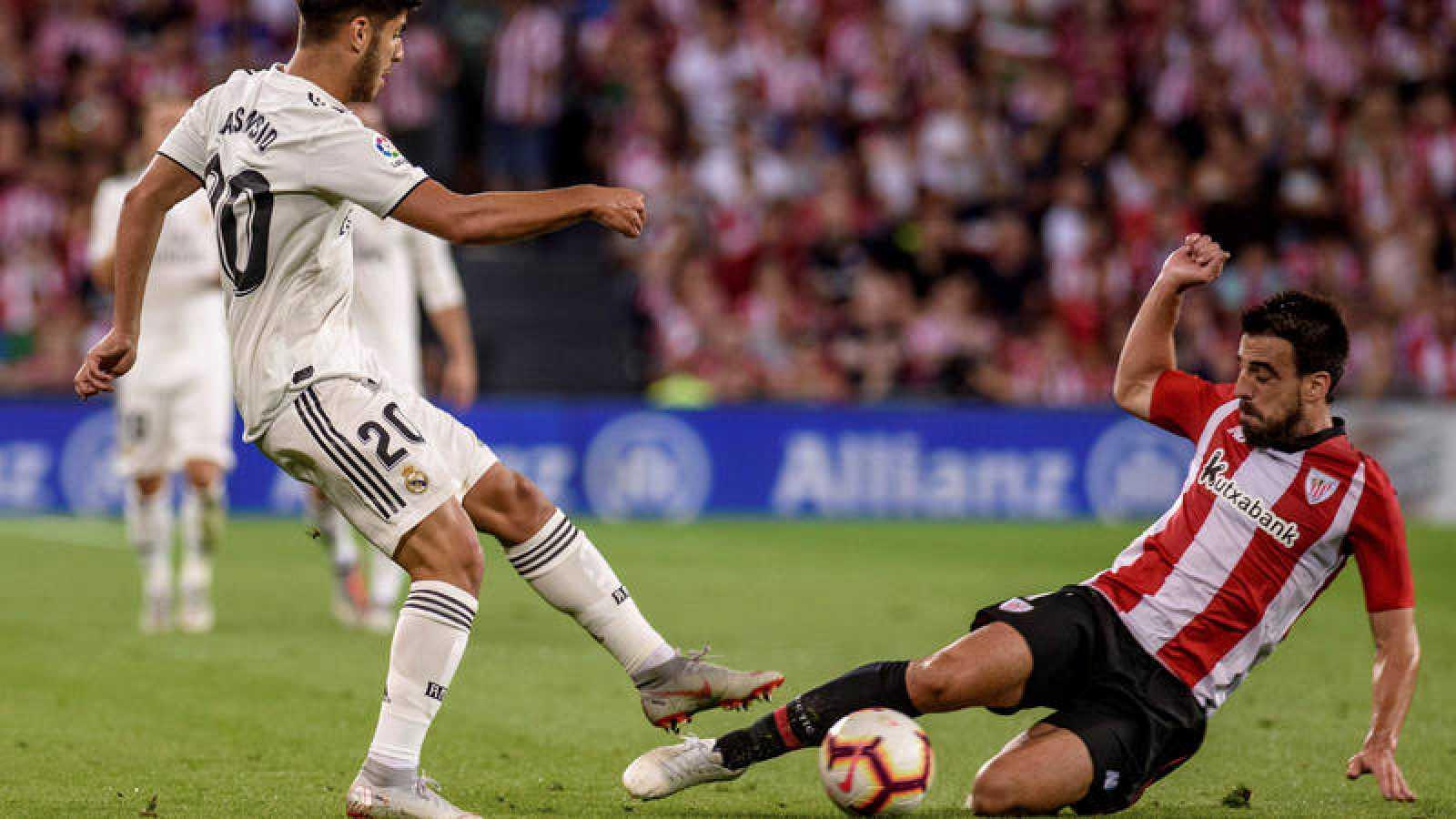 Marco Asensio pugna con Beñat durante un partido en San Mamés.