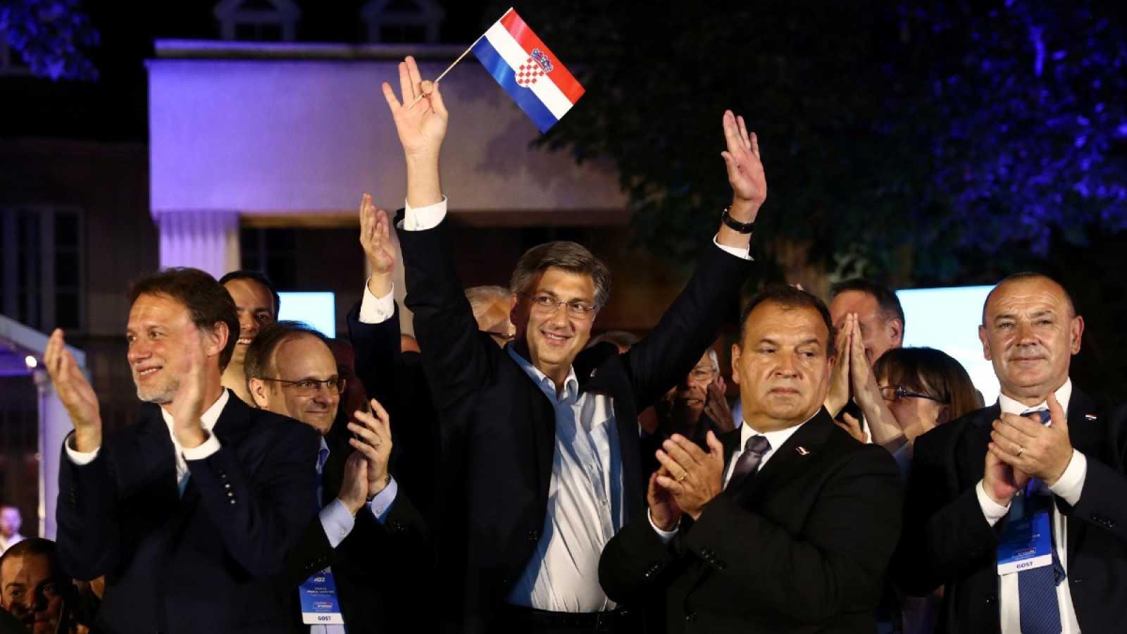El primer ministro croata y líder de la Unión Democrática Croata (HDZ), Andrej Plenkovic, sostiene una bandera de Croacia después de que se anunciaran los resultados de las elecciones.