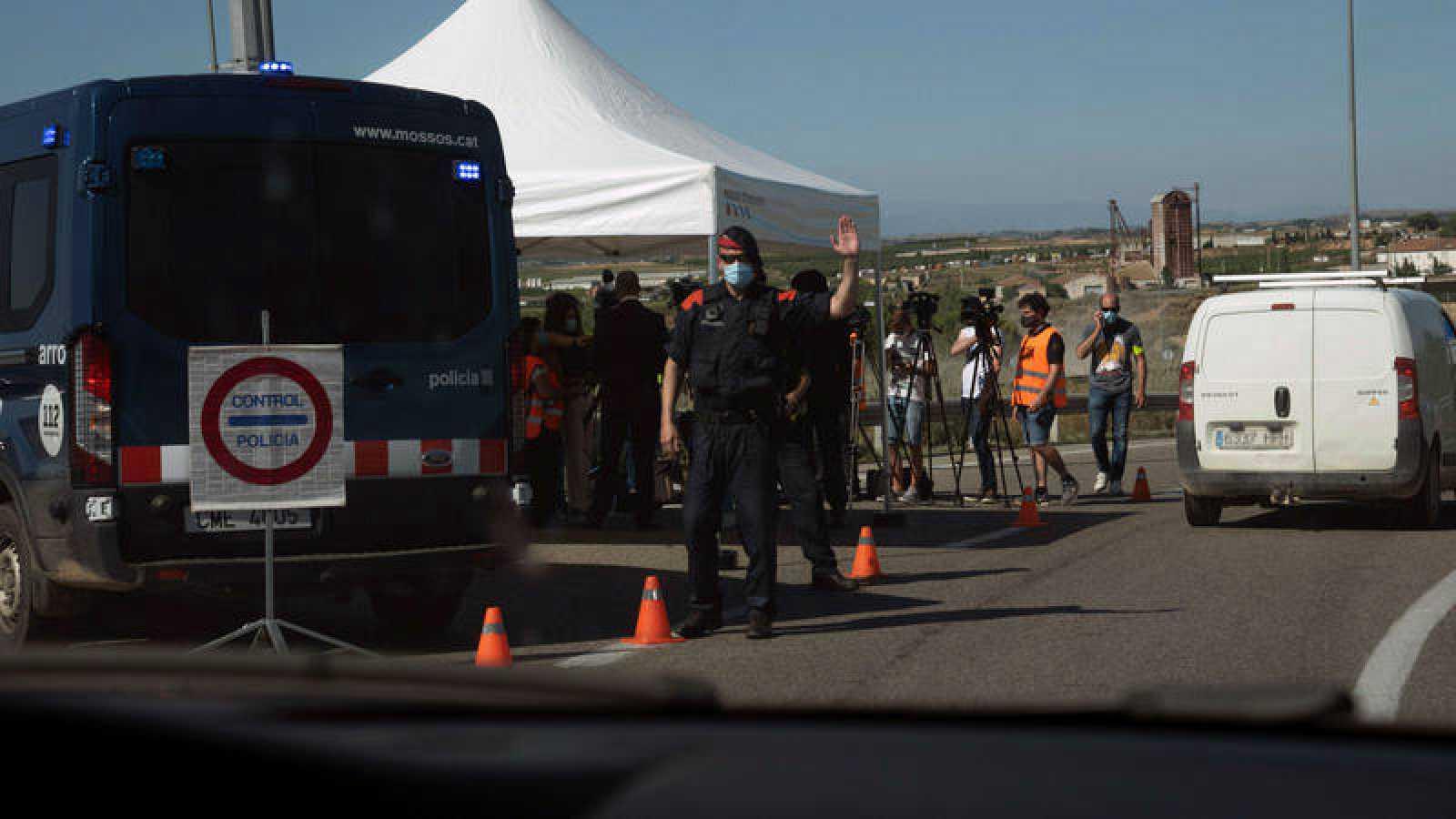 Un Mosso d'Esquadra realiza un control de carreteras en la comarca del Segrià (Lleida), tras su confinamiento a causa de los brotes por coronavirus.