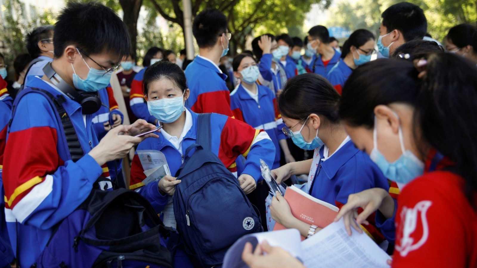"""Un grupo de estudiantes con mascarillas se preparan antes de entrar al examen anual nacional de ingreso a la universidad, o """"gaokao"""", que ha sido pospuesto un mes debido al brote de coronavirus, en Pekín, China."""