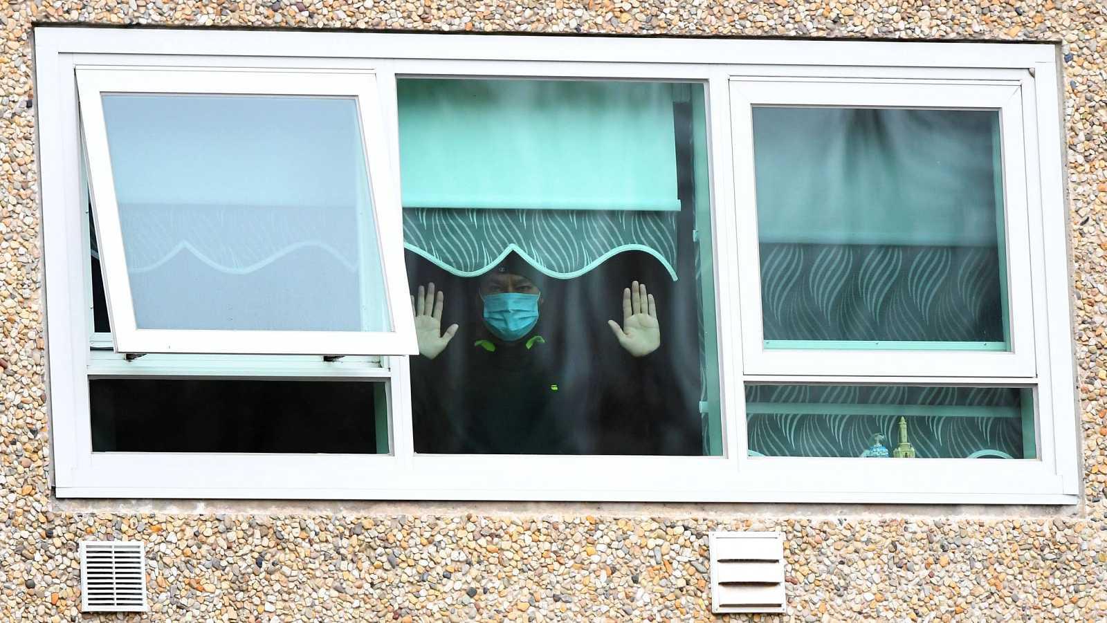 Un hombre confinado en el foco principal de Melbourne, en Australia, observa a través de una ventana