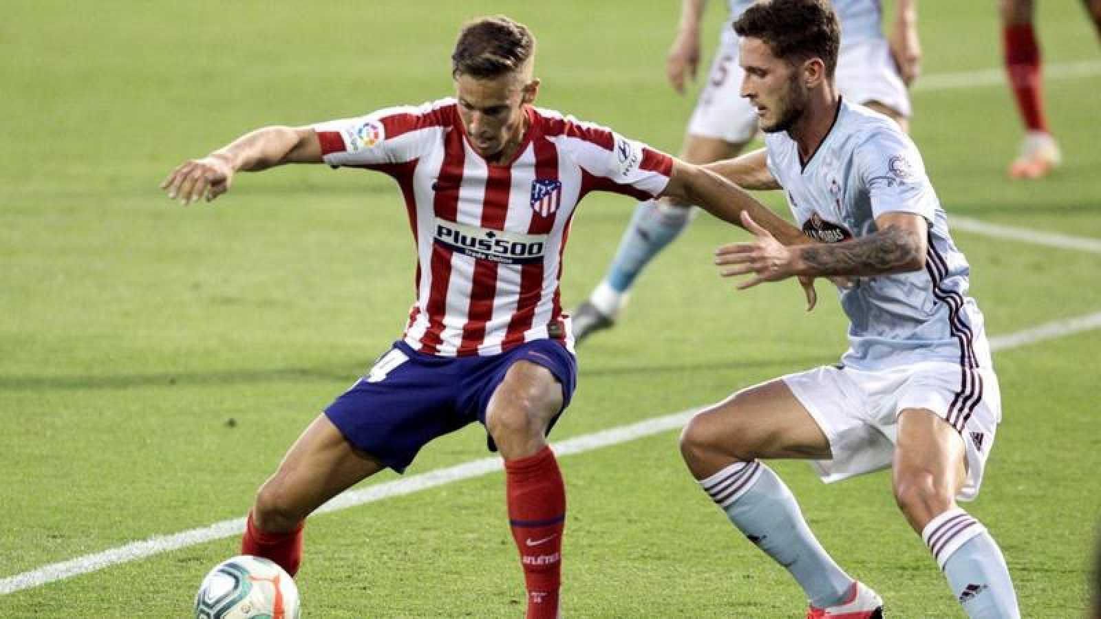 El centrocampista del Atlético de Madrid, Marcos Llorente (i), controla el balón ante el defensa del Celta de Vigo, Jorge Sáenz.