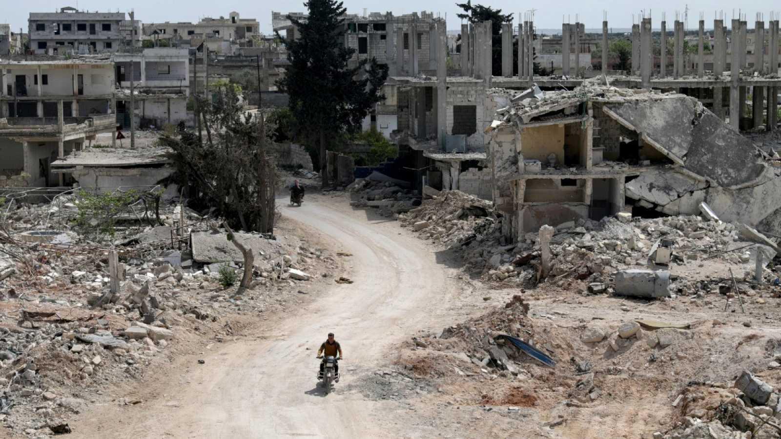 Un hombre en motocicleta pasa entre edificios derruidos en la ciudad de Nairab, en la región de Idlib, Siria, el 17 de abril de 2020.
