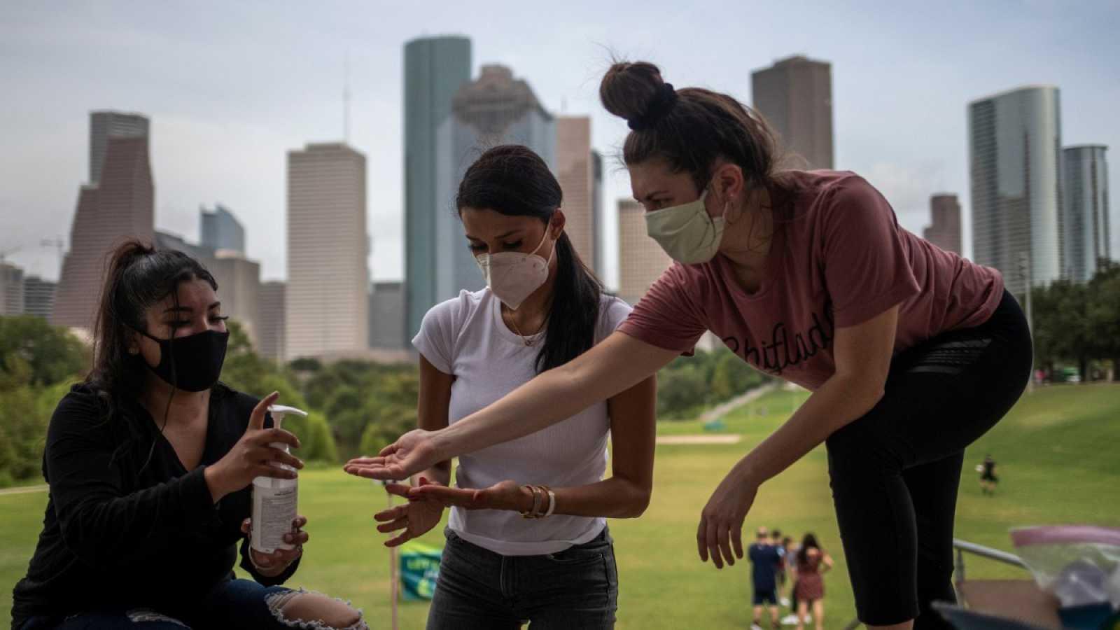 Tres jóvenes con mascarilla comparten desinfectante de manos con el 'skyline' de Houston, Texas, de fondo.