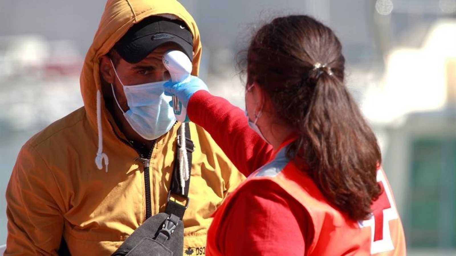 Personal de Cruz Roja toma la temperatura con un termómetro de infrarrojos a un inmigrante recién llegado a puerto.