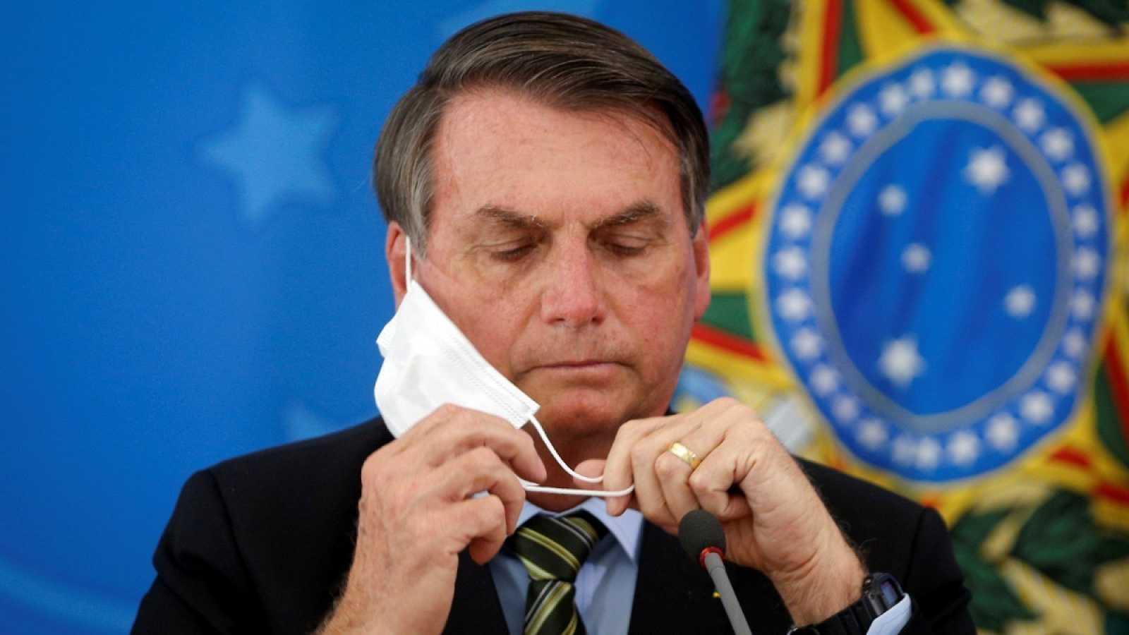 El presidente de Brasil, Jair Bolsonaro, se coloca la mascarilla en una rueda de prensa en una foto de archivo