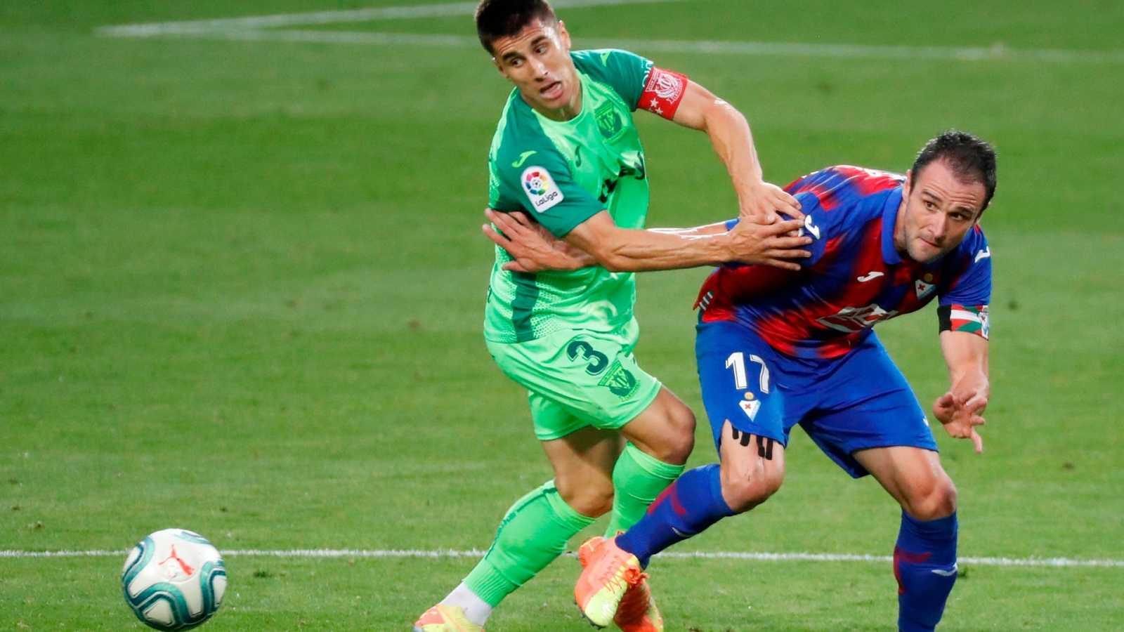 El defensa de Leganés Unai Bustinza (i) presiona al delantero del Eibar Kike García