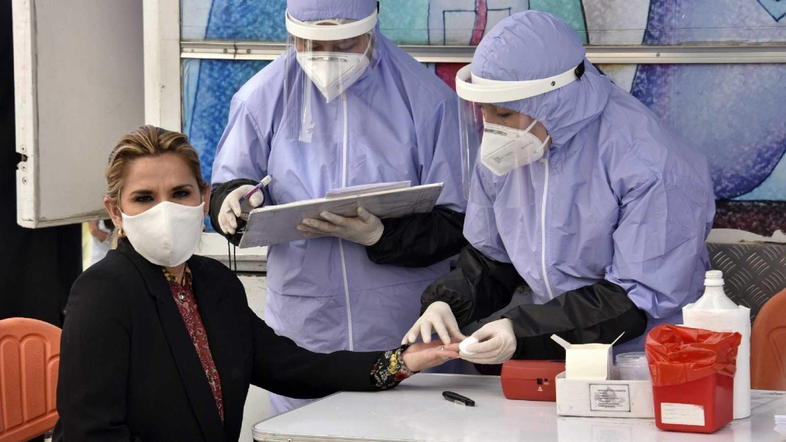 La presidenta boliviana Jeanine Anez se hace un análisis de sangre antes de donar sangre el Día del Donante de Sangre, en el palacio presidencial de La Paz durante la pandemia, en junio