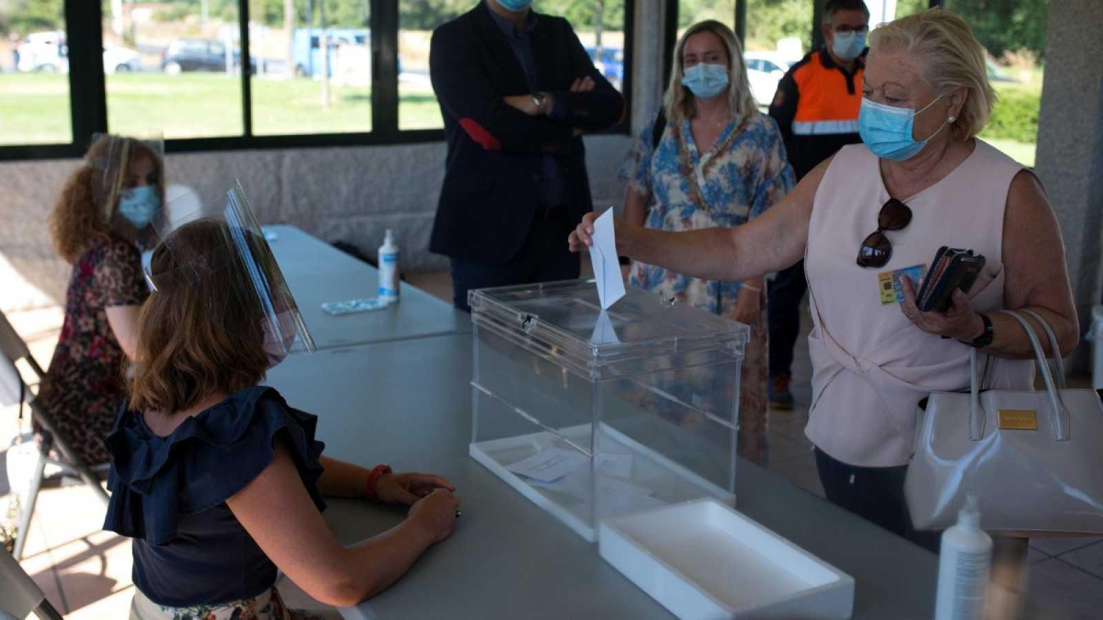 Una mujer introduce una papeleta en una urna durante la simulación de una votación en Galicia