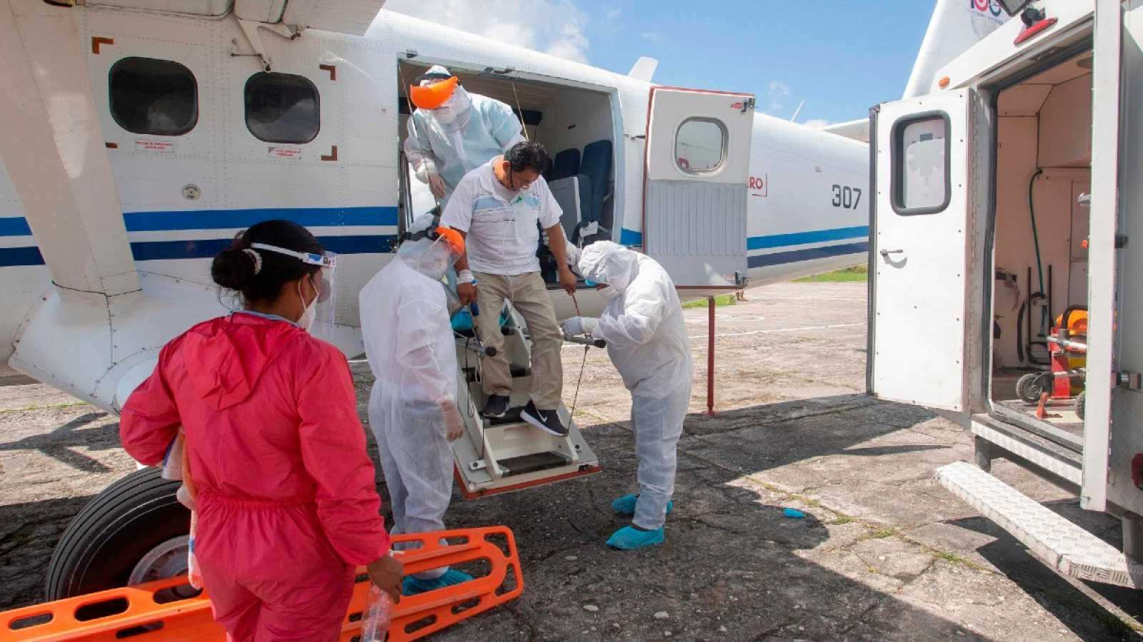 Un trabajador médico que muestra síntomas de la COVID-19 desciende de una aeronave en Iquitos, en el Amazonas en el norte de Perú