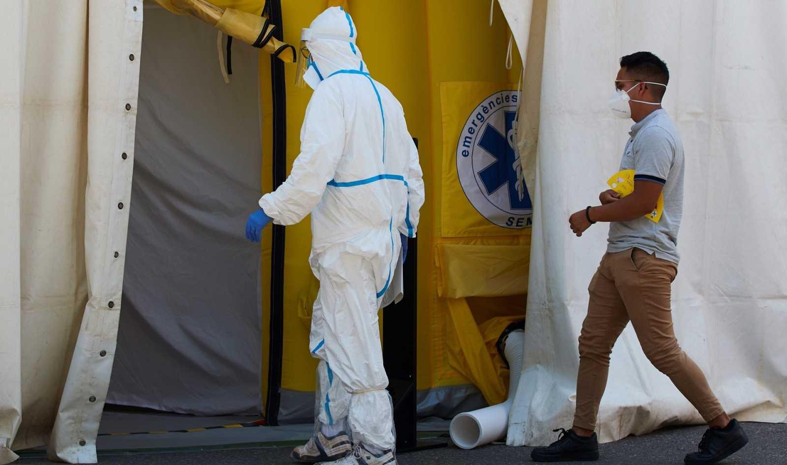 Un sanitario y un paciente entran en el hospital de campaña en Lleida