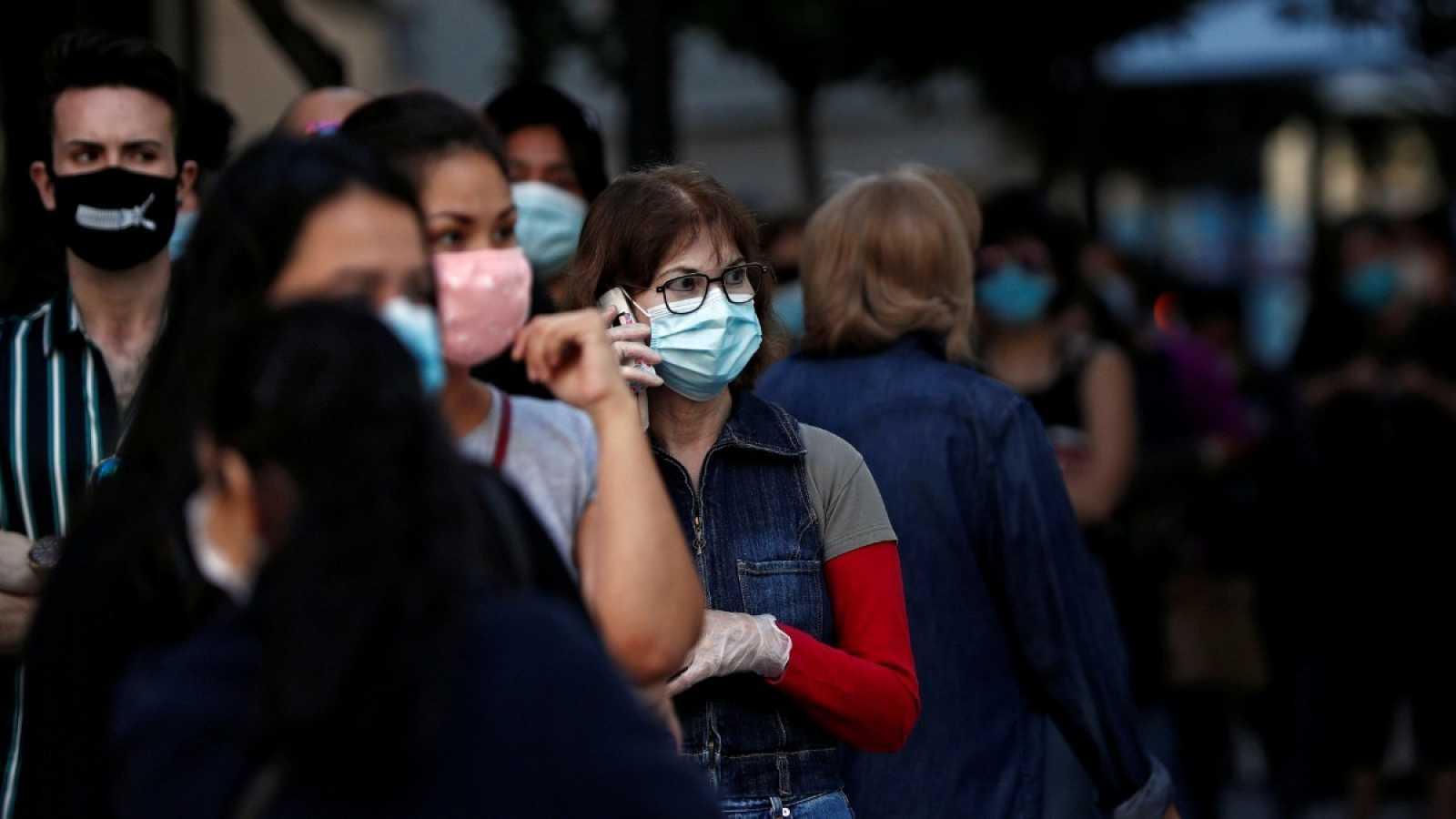 Una mujer con mascarilla y guantes habla por teléfono en la calle