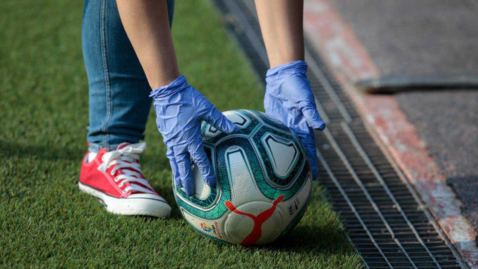 Una persona toca con guantes sanitarios en las manos toca un balón de la Liga