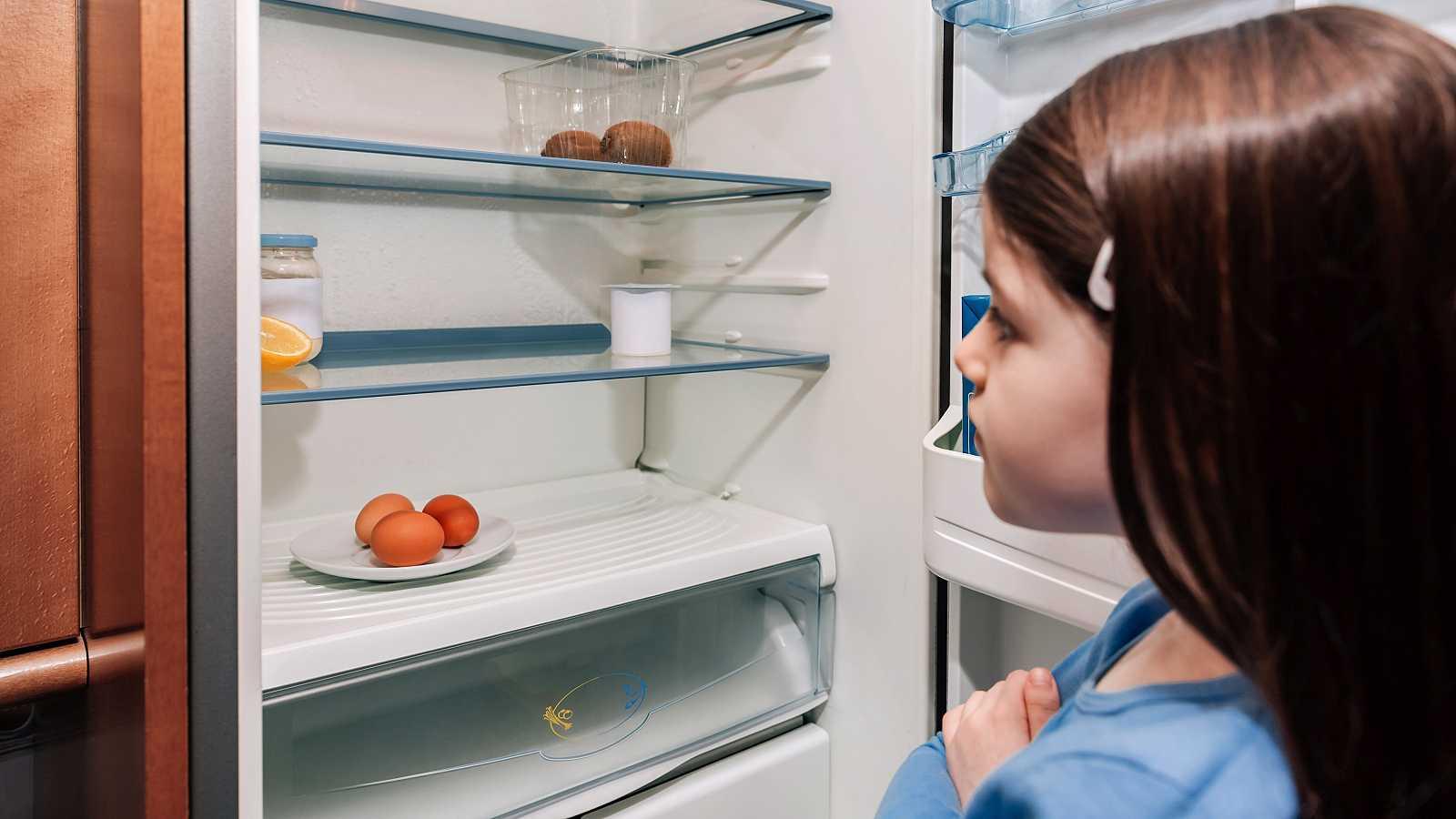 Una niña abre la nevera casi vacía de alimentos.