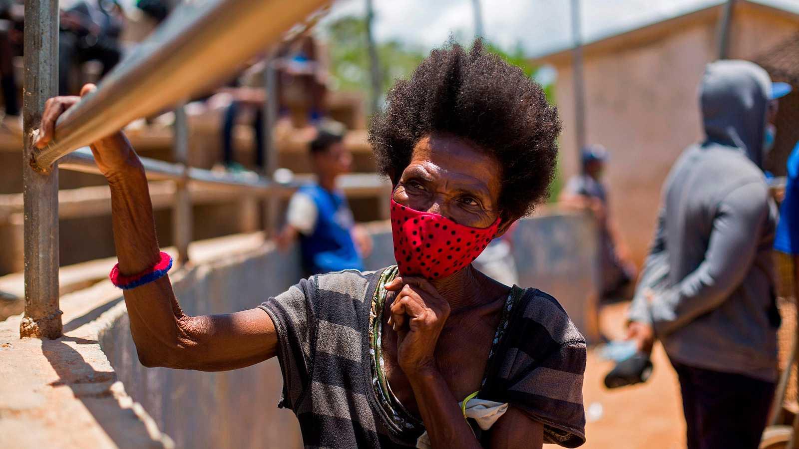 Una mujer usa mascarillas contra la propagación del coronavirus mientras asiste a un partido de béisbol en Boca Chica, República Dominicana