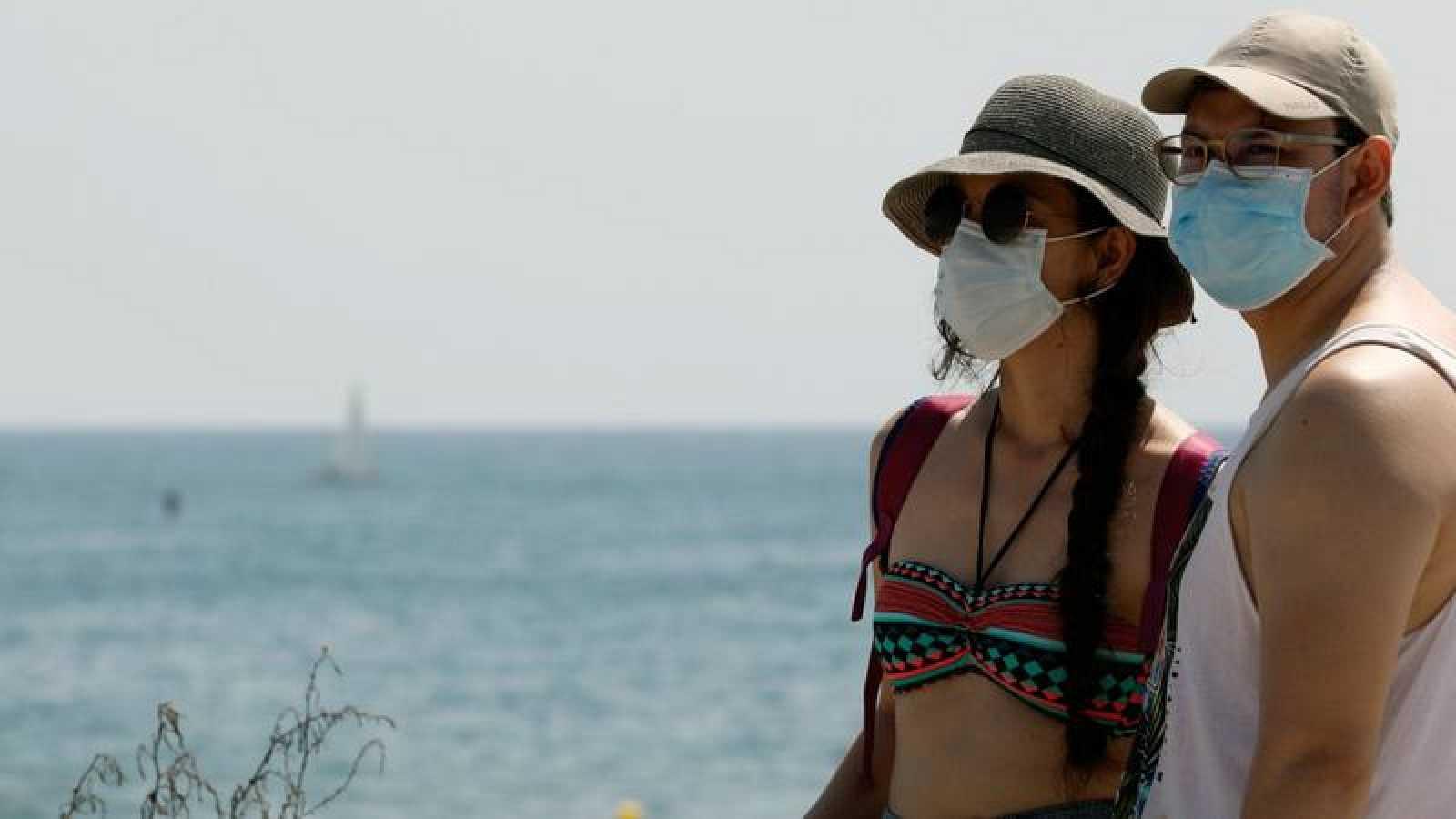 Dos personas protegidas con mascarillas en la playa de la Malvarrosa de Valencia